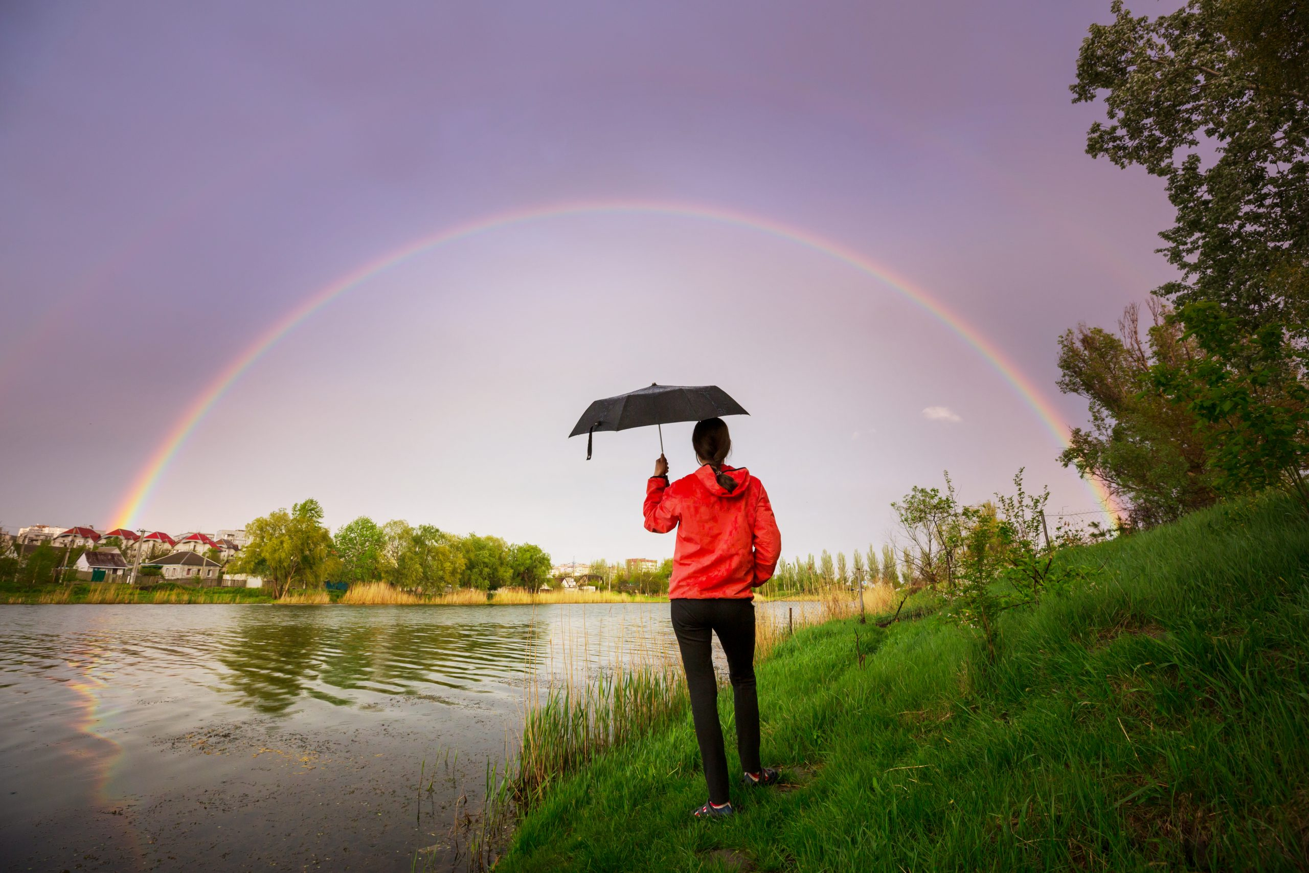 Lady standing with umbrella by a river with rainbow in the distance